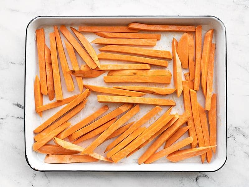 Cut sweet potatoes arranged on the baking sheet
