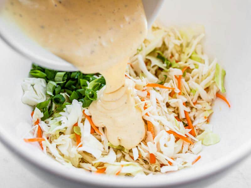 Add coleslaw dressing to cabbage in the bowl