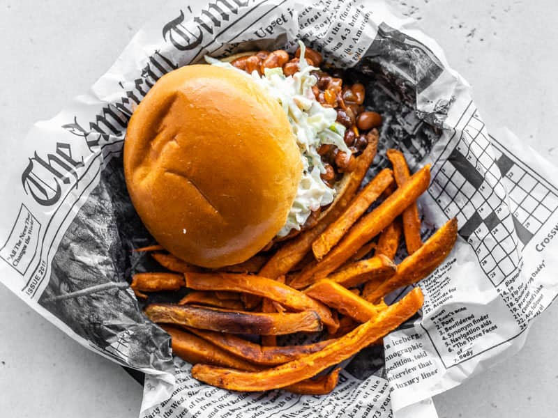 Spicy Sweet Potato Fries next to a BBQ Bean Slider in a dish lined with newsprint, viewed from above