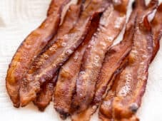 Several strips of bacon on a paper towel covered plate, viewed from the side