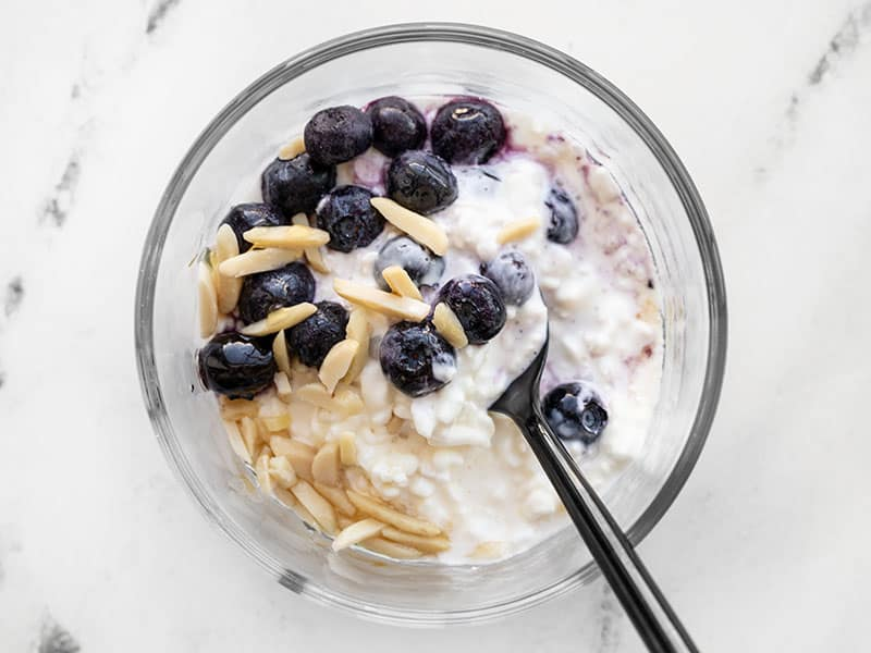 Cottage cheese, blueberries, sliced almonds, and honey in a glass meal prep container