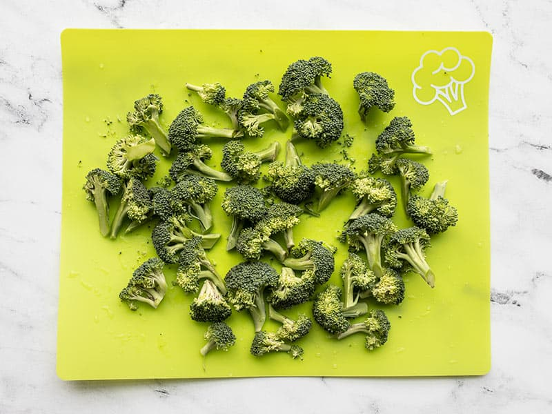 Chopped broccoli florets on a green cutting board