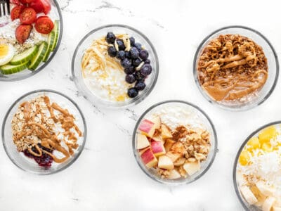 Six glass bowls with different flavors of cottage cheese breakfast bowls inside.
