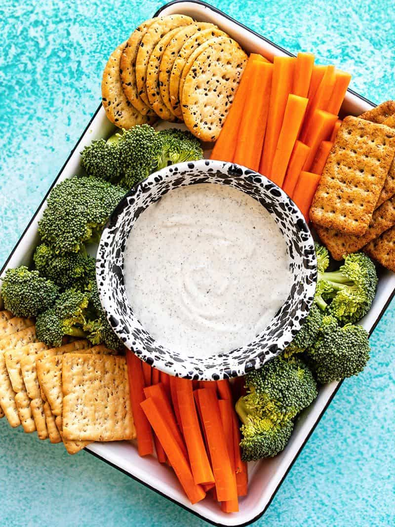 A platter full of crackers and vegetables with a bowl of garlic herb cottage cheese dip in the center
