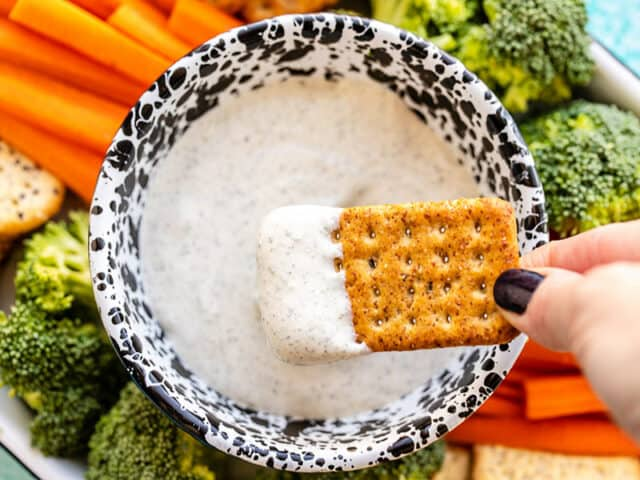 A cracker being dipped into the whipped cottage cheese dip, the platter of vegetables and crackers in the background