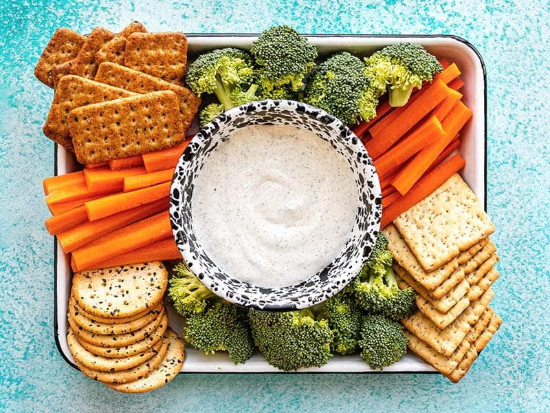 A platter full of crackers and vegetables with a bowl of Whipped Cottage Cheese Dip in the center