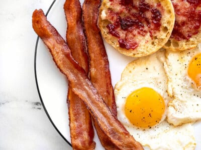 Three strips of bacon on a plate with fried eggs and an English Muffin