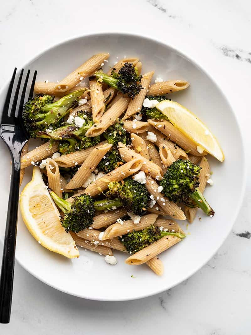 A plate with roasted broccoli pasta, lemon wedges, feta, and a black fork on the left