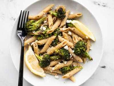 A bowl full of Roasted Broccoli Pasta with lemon and feta and a black fork on the left side