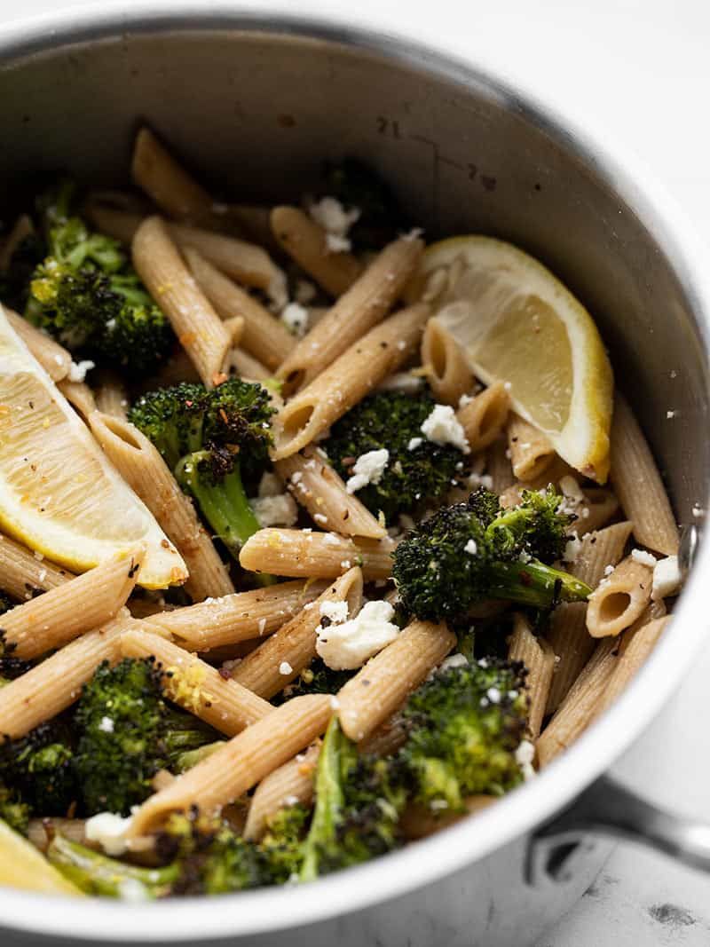 Front view of a pot full of Roasted Broccoli Pasta with Lemon and feta, garnished with lemon wedges