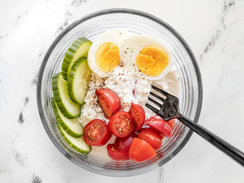 A glass bowl with cottage cheese, hard boiled egg, tomatoes, cucumber, and pepper.