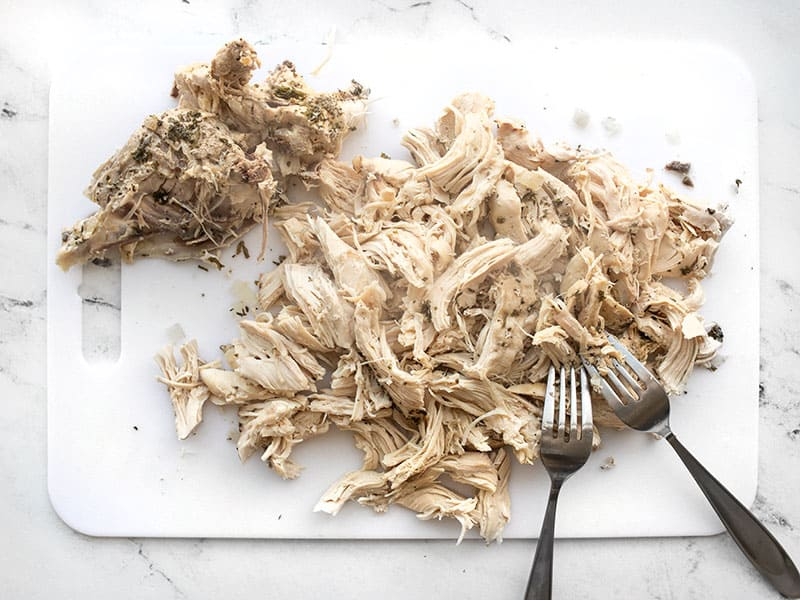 Chicken meat shredded with forks, bones on the side