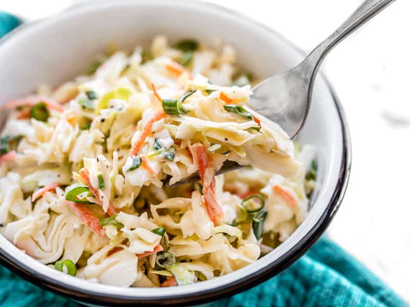 Side view of a bowl of creamy coleslaw with a fork lifting a bite