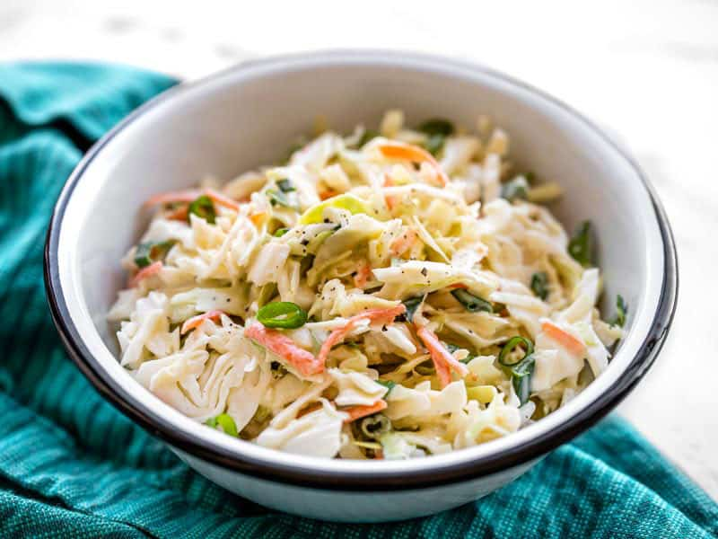 front view of a bowl of creamy coleslaw on a blue napkin