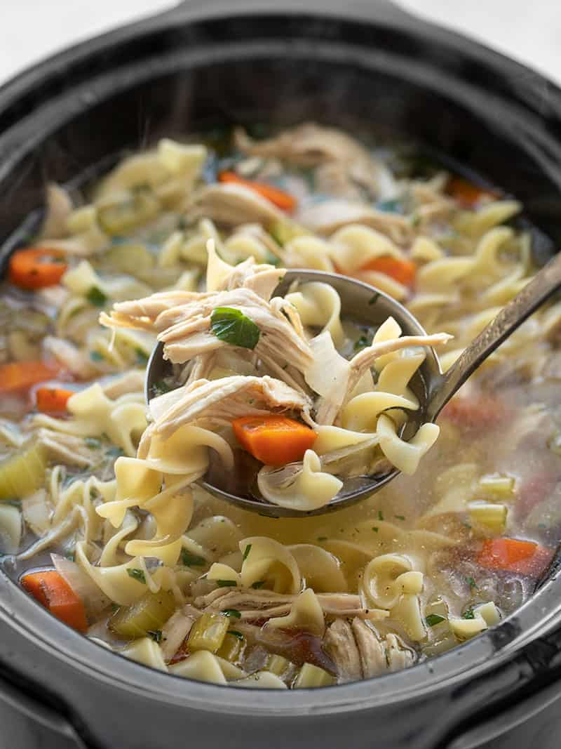 Front view of a ladle lifting some chicken noodle soup out of the slow cooker