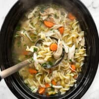 Overhead view of a ladle lifting chicken noodle soup out of the slow cooker