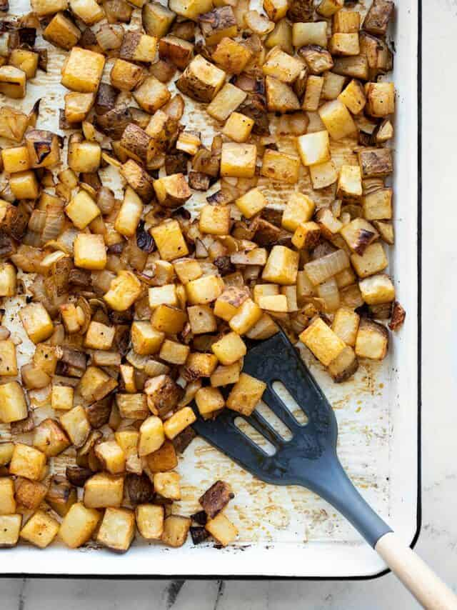 A sheet pan full of roasted breakfast potatoes with onions