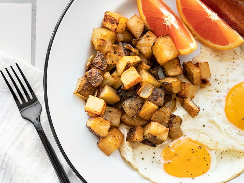 Close up of roasted breakfast potatoes on a plate with eggs and orange slices