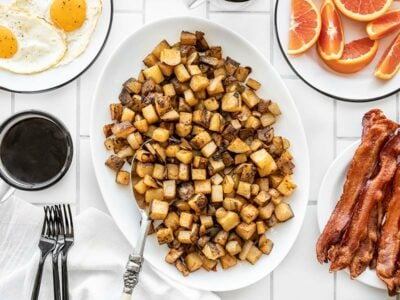 A platter full of roasted breakfast potatoes with eggs, coffee, oranges, and bacon on the side