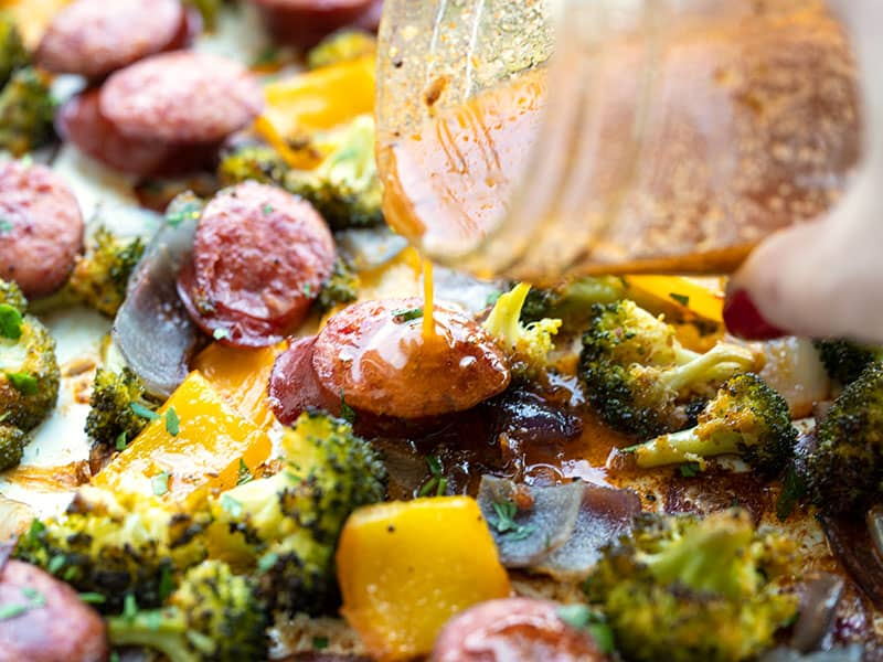 vinaigrette being drizzled over sausage and vegetables
