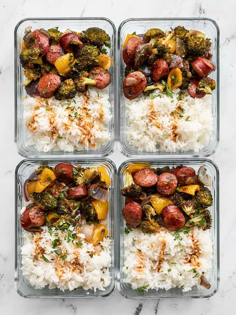 meal prepped roasted sausage and vegetables in rectangular glass containers