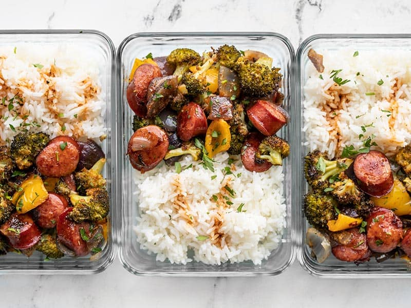 Three glass meal prep containers with rice and Smoky Roasted Sausage and Vegetables