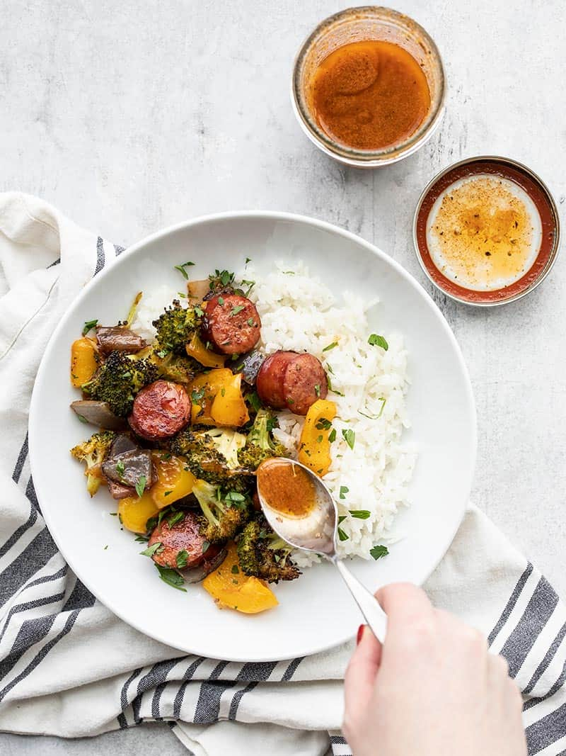 A bowl of rice with smoky roasted sausage and vegetables, vinaigrette being drizzled on top with a spoon.