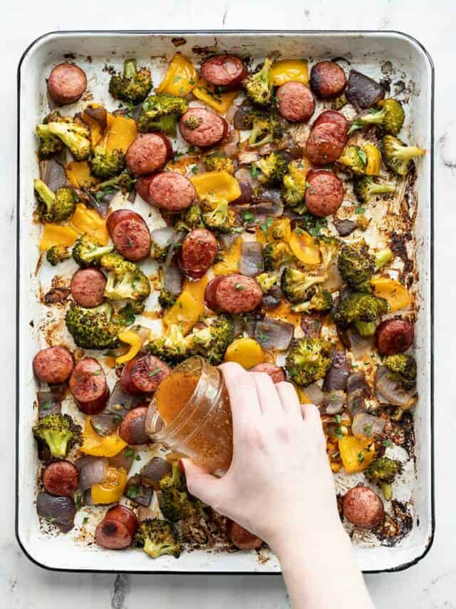 A hand drizzling smoky vinaigrette over a sheet pan full of roasted sausage and vegetables