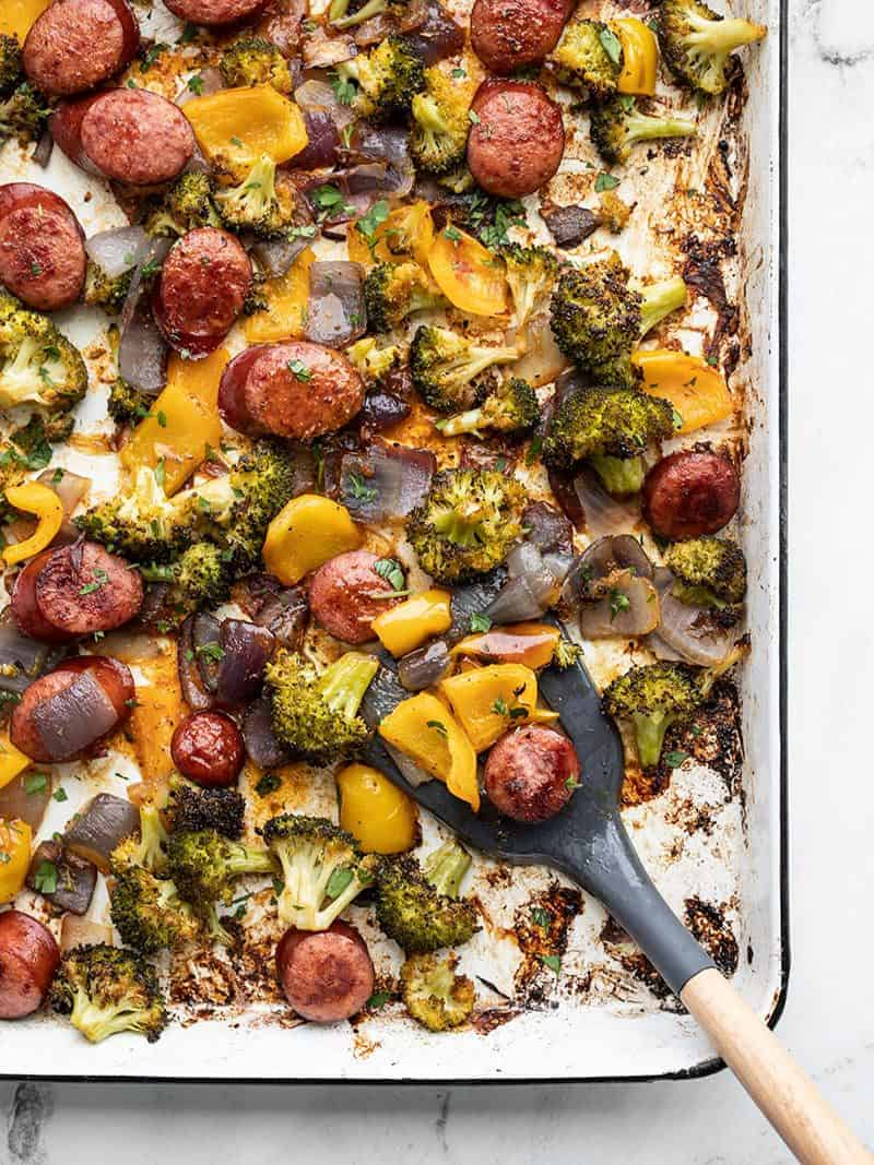 Smoky Roasted Sausage and Vegetables on the sheet pan with a spatula scooping some in the bottom corner