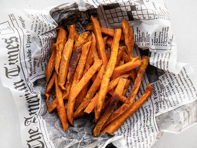 A pile of sweet potato fries in a newsprint lined dish, viewed from above