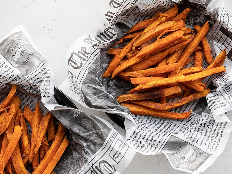 Overhead view of two dishes lined with newsprint containing spicy sweet potato fries