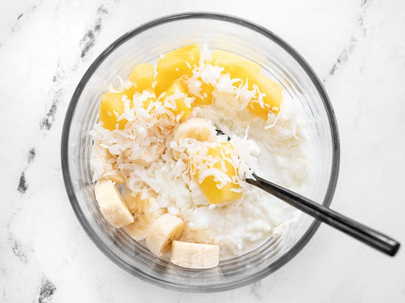 Cottage cheese, pineapple, banana, and coconut in a glass meal prep container
