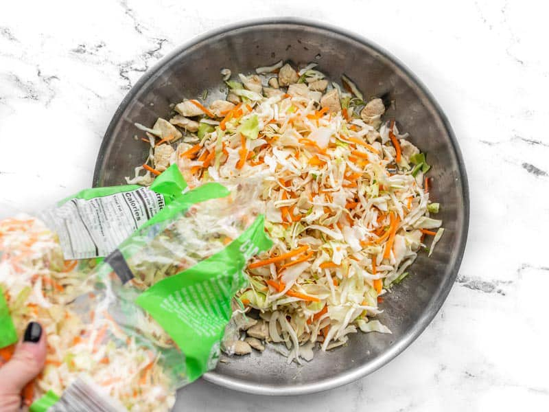 Coleslaw mix being poured into the skillet