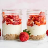 Two jars of no bake strawberry cheesecake side by side with whole strawberries on the side