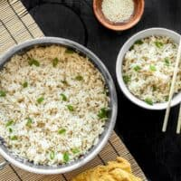 A pot full of sesame rice with a bowl of sesame rice on the side, both garnished with green onion