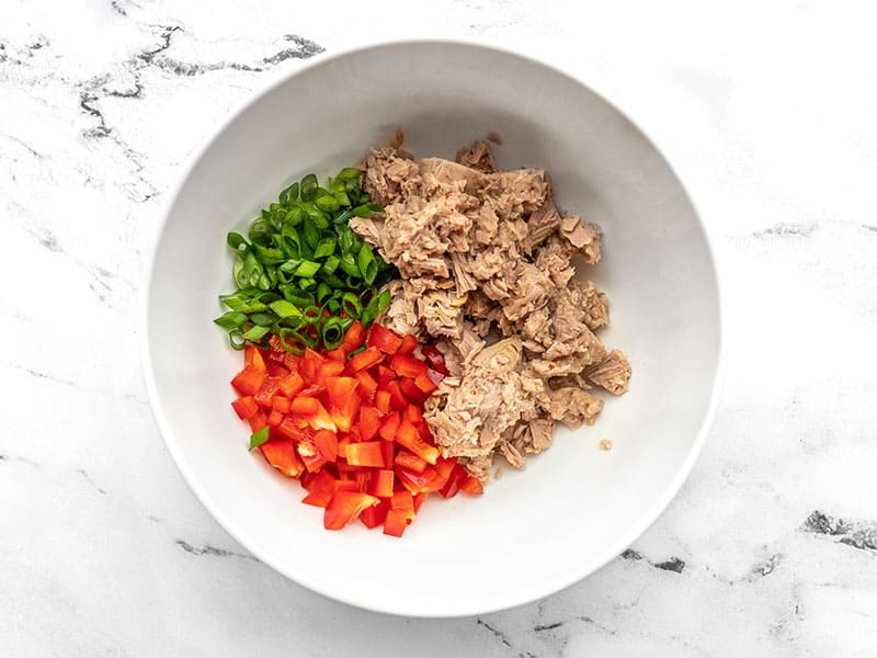 Tuna, diced red bell pepper, and sliced green onion in a bowl