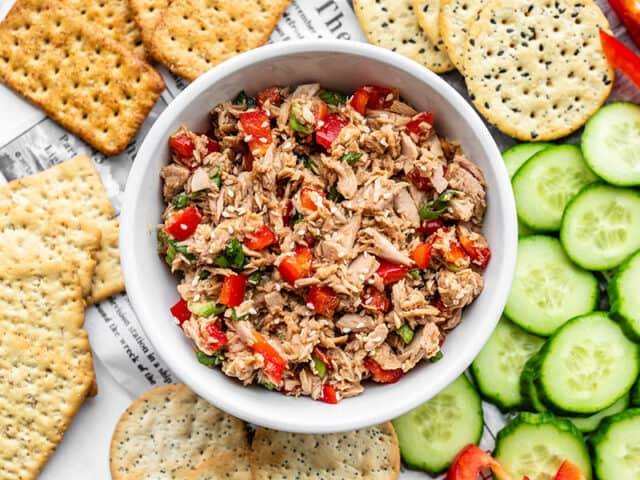 A bowl of sesame tuna surrounded by cucumber and crackers