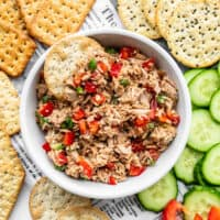 A bowl of Sesame Tuna Salad surrounded by crackers and cucumber slices
