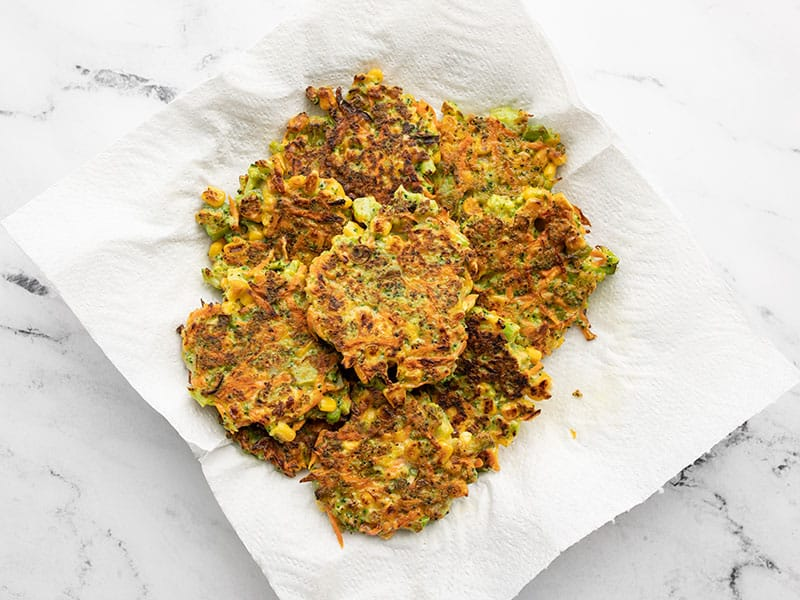 Cooked vegetable fritters on a paper towel lined plate