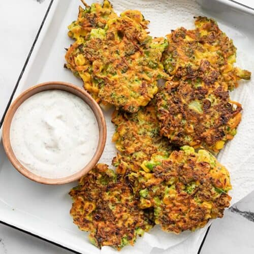Overhead view of a white tray lined with paper towel, with vegetable fritters and a small bowl of garlic herb dipping sauce