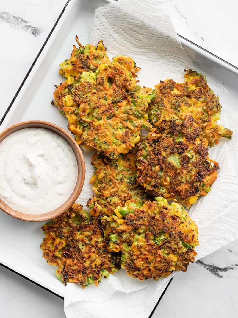 Overhead of vegetable fritters on a paper towel lined white tray, with a bowl of garlic herb dipping sauce on the side