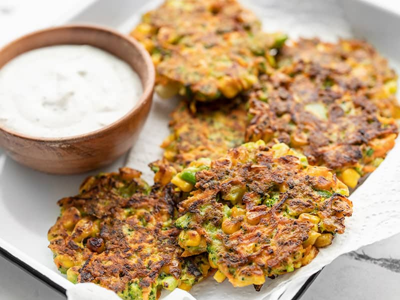Front view of vegetable fritters on a tray with a small bowl of garlic herb sauce