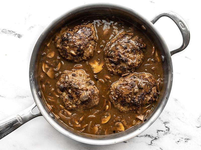 Simmered Salisbury Steaks in the skillet with mushroom gravy.