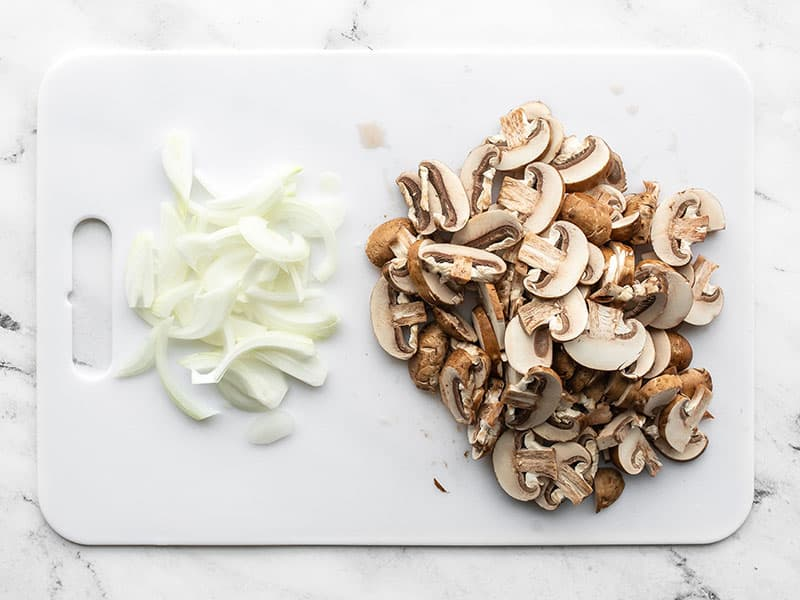 Sliced mushrooms on a cutting board with the sliced onion.