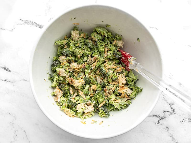 Finished broccoli cheddar chicken salad in the bowl with a spatula