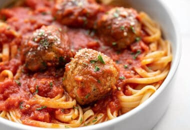 Close up side view of chicken Parmesan meatballs on a pile of spaghetti with sauce