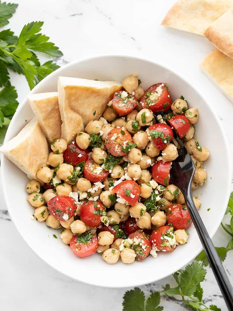 Overhead view of Chimichurri Chickpea Salad with triangles of pita bread stuck in the side.