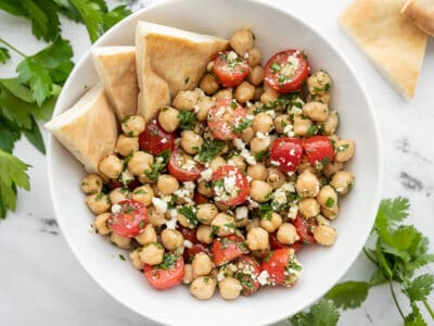 Overhead view of a bowl of Chimichurri Chickpea Salad with pita in the side of the bowl