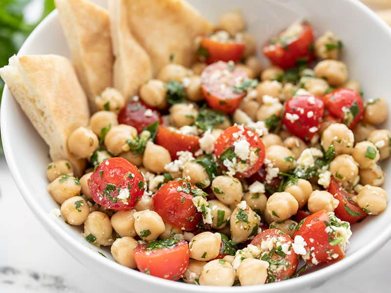 Close up side view of the bowl of Chimichurri Chickpea Salad with pita triangles in the side of the bowl