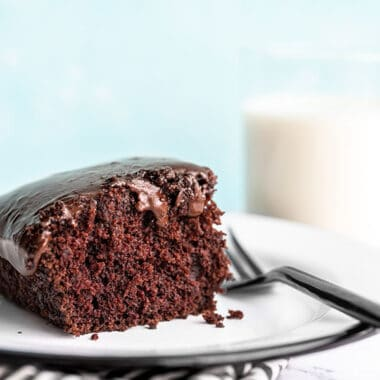 """One slice of chocolate depression cake or """"crazy cake"""" viewed from the side, a glass of milk in the background"""